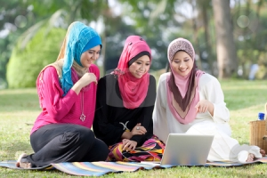 Three young Muslim women are playing a laptop while relaxing in the park